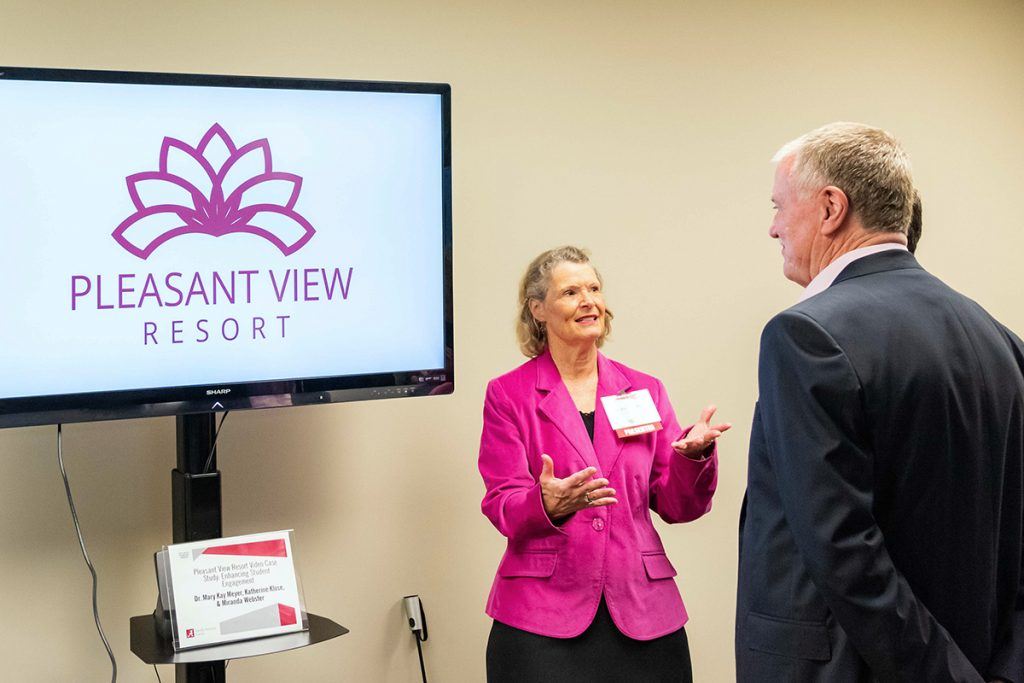 Faculty presents video training project to two attendees